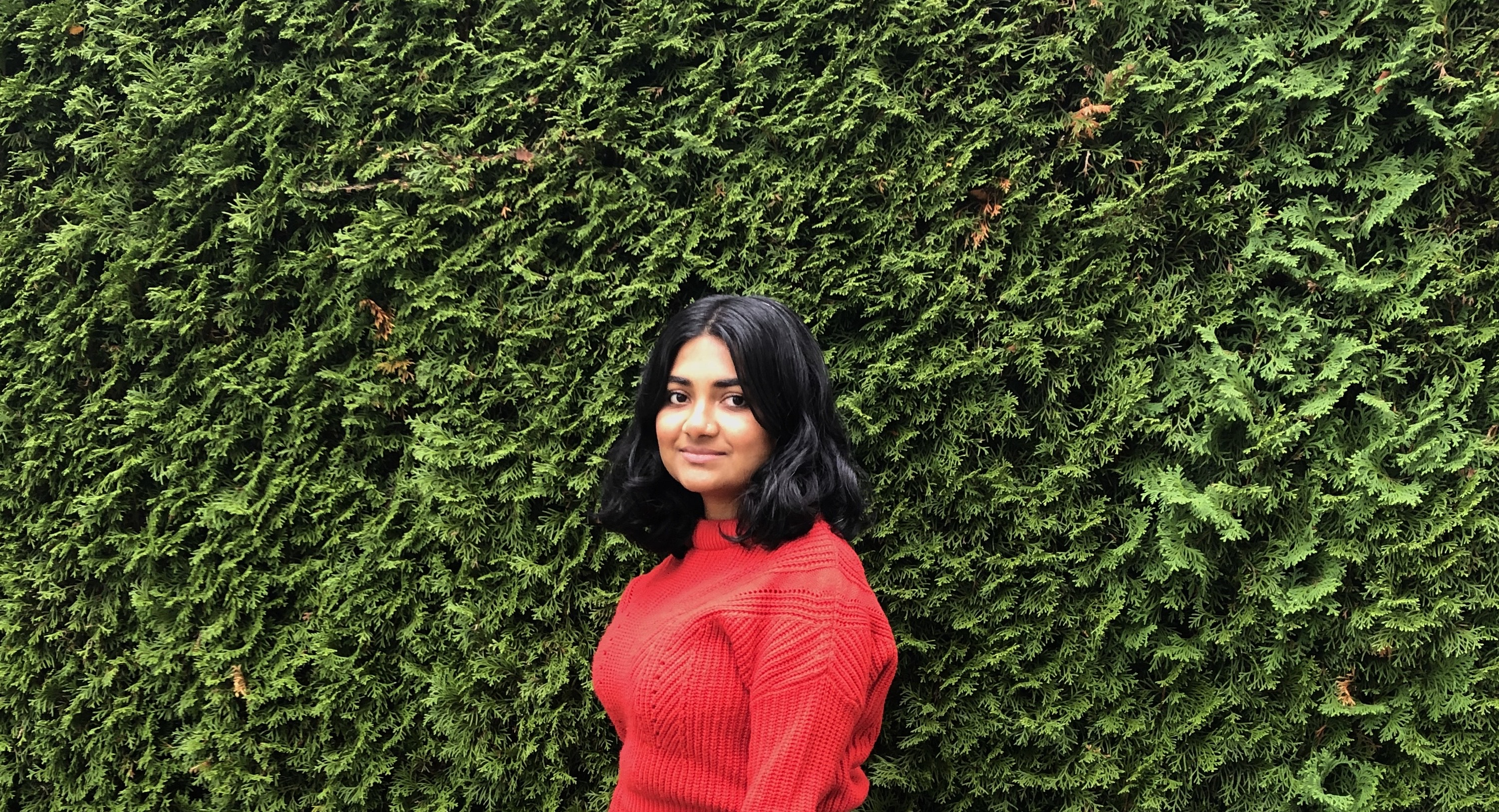 Hina wears a red sweater and stands in front of a hedge