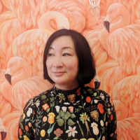 Andrea Gin in a botanical shirt standing in front of a wall with bold flamingo wallpaper