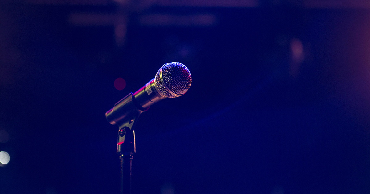 A closeup of a microphone on an empty stage